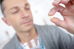 Man taking tablet with glass water Stock Image
