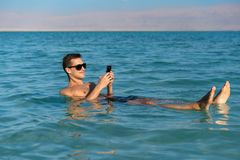 Young man floating on the water surface of the dead sea and using his smartphone stock image