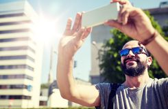 Man taking video or selfie by smartphone in city. Travel, tourism, communication, technology and people concept - smiling man with backpack taking video or Stock Photo