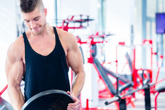 Man taking weights from stand in fitness gym Royalty Free Stock Images