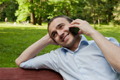 Man talk by phone in the park. Man talk by phone on the bench in the park Stock Photography