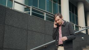 Man talk texting on phone. Casual urban professional entrepreneur using smartphone smiling happy outside office building. Man texting on phone. Casual urban stock video