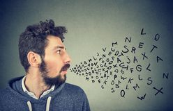 Man talking with alphabet letters coming out of his mouth. Communication, information, intelligence concept Stock Photos
