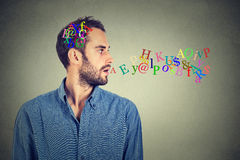 Man talking with alphabet letters in his head and coming out of open mouth. Side view portrait man talking with alphabet letters in his head and coming out of Stock Photos