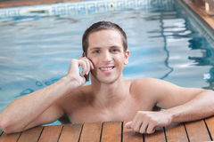 Man talking on cell inside the pool Stock Photo