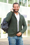 Man talking on cell phone with backpack outside Royalty Free Stock Photography
