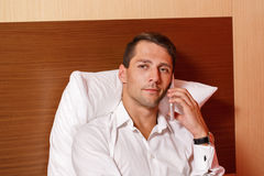 Man talking on cell phone. Businessman talking on cell phone, leaning on the pillow Royalty Free Stock Photo