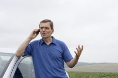 Man talking on cell phone beside a car. Angry man talking on cell phone beside a car Stock Photography