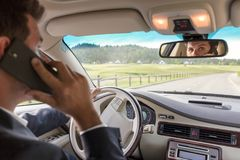 Man talking on cell phone while driving not paying attention to the road. Businessman talking on cell phone while driving not paying attention to the road stock photo
