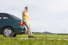 Man talking on cell phone beside his car Royalty Free Stock Image