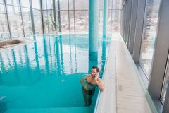 Man talking on cell phone inside the swimming pool at luxury hotel.  Royalty Free Stock Photography