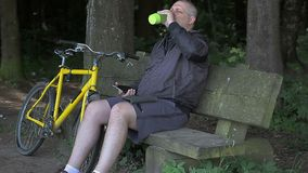 Man talking on cell phone near bicycle in the park stock video