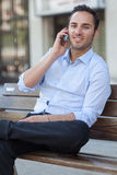 Man talking on cell phone. Man sitting on bench with mobile phone stock photography