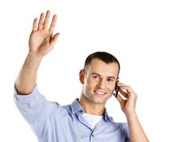 Man talking on the cell phone waves the hand Stock Photography