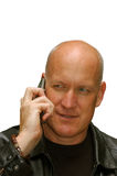 Man talking on a cell phone (on white). An attractive adult man in a black leather jacket is talking on a cell phone with his girlfriend, smiling in a warm and Stock Images