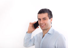 Man talking on cell phone. Young handsome man in shirt talking on cell phone against white background Royalty Free Stock Photography