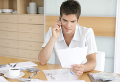 Man Talking on Cell Working on Finances Royalty Free Stock Image