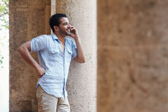 Man talking on cellphone. Mid adult hispanic man talking on mobile phone and leaning on columns outdoors. Horizontal shape, side view, copy space stock images