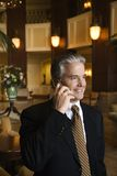 Man talking on cellphone. Caucasian prime adult male businessman talking on cellphone in hotel lobby Royalty Free Stock Image