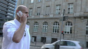 Man Talking with Cellphone in City and Business Tower stock footage