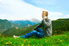 Man talking on cellphone outdoor. Casual wearing man talking on cellphone outdoor. Mountains stock image