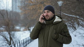 Man talking on cellphone in the park at winter time stock footage