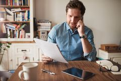 Man talking on a cellphone while reading paperwork at home. Young man sitting at a table in his living room talking on a cellphone and reading paperwork while royalty free stock photos