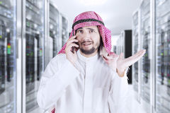 Man talking on cellphone in server room. Young Arabian man speaking on the mobile phone while standing in the server room Royalty Free Stock Photos