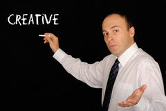 Man talking at chalkboard. A view of an instructor or teacher or speaker wearing white shirt and tie, talking at a chalkboard with the word creative on it Stock Image