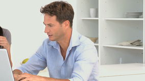 Man talking with her girlfriend while he is working on his laptop. Man talking with her girlfriend while he working on his laptop against a white background stock footage