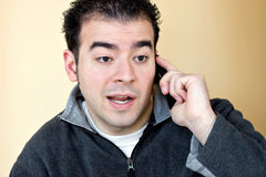 Man Talking On His Cell Phone. A young man talking on his cell phone with a concerned look on his face Stock Images