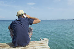 Man talking on his cell phone at the pier. Man talking on his cell phone at the dock at sea Stock Images