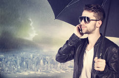 Man talking on his cellphone in the rain Stock Photo
