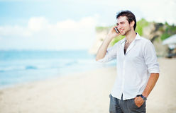 Man talking on his phone at the beach Stock Images