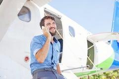 Man talking on his phone next to airplane Stock Photos