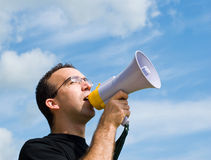 Man Talking Into Megaphone. A young man wearing glasses is talking into a megaphone outside with blue sky behind him Royalty Free Stock Photo