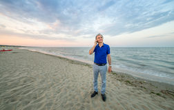 Man talking on mobile on beach Stock Images