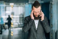 Man talking mobile headache business phone call. Man talking on mobile. headache and unpleasant business phone call stock photo