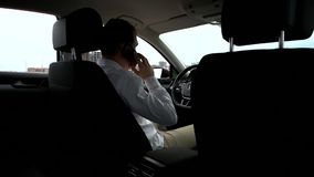 Man talking on mobile phone in car stock footage