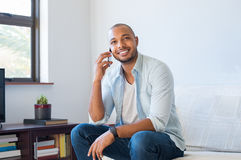 Man talking on mobile phone. Cheerful black man in a happy conversation over mobile phone. Pensive african guy sitting on sofa talking on cellphone. Smiling man stock images
