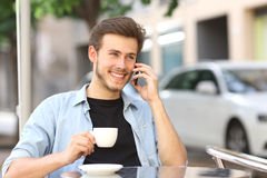 Man talking on the mobile phone in a coffee shop. Sitting in the terrace outdoors and holding a cup Stock Photo