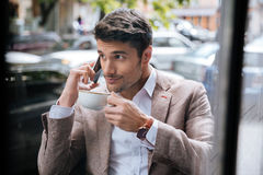 Man talking on mobile phone and drinking coffee in cafe Royalty Free Stock Image