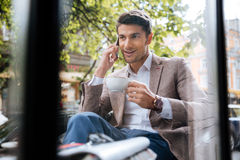 Man talking on mobile phone and drinking coffee in cafe Royalty Free Stock Photos