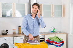 Man Talking On Mobile Phone While Ironing Clothes Stock Photography