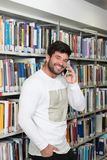Man Talking on Mobile Phone in Library. Portrait of a Happy Handsome Man Talking on Mobile Phone in Library at the University Stock Photography