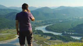 Man is talking on a mobile phone on a mountain stock video