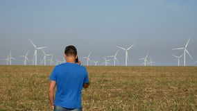 Man talking on mobile phone near about wind turbines electricity production, green energy concept. Man in blue t-shirt talking on mobile phone near about wind stock footage