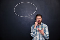Man talking on mobile phone over chalkboard with speech bubble Royalty Free Stock Images