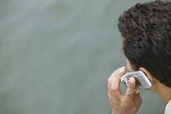 Man talking on mobile phone over water Royalty Free Stock Image