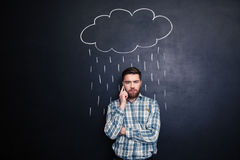 Man talking on mobile phone under rain drawn at blackboard Royalty Free Stock Photo
